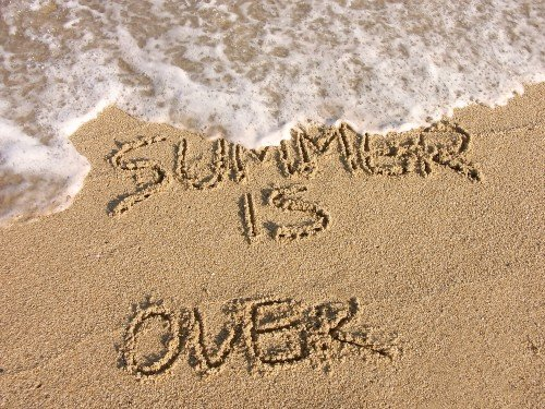 summer is over written in sand with wave approaching_1803491