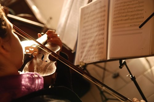 sheetmusic with violin being played shot from over shoulder looking down at 45 degree