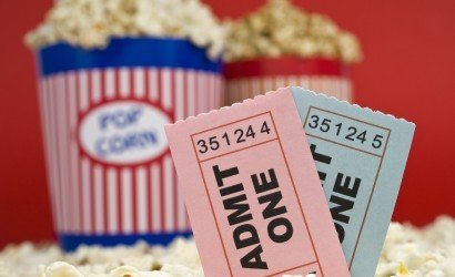 movie stub two sticking out of popcorn with two pop corn bags in background with red backdrop