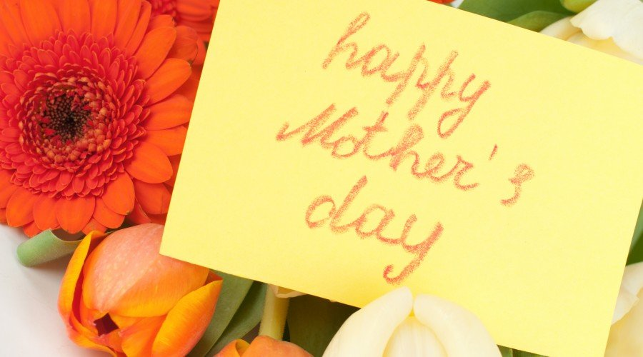 happy mothers day card written in crayon over top flowers_73651750