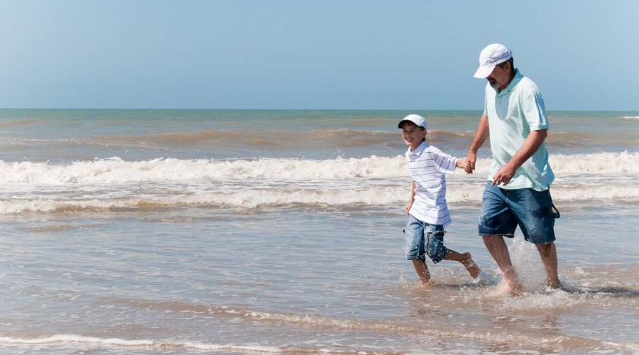 Son and dad walking through water at the beach on Father's Day