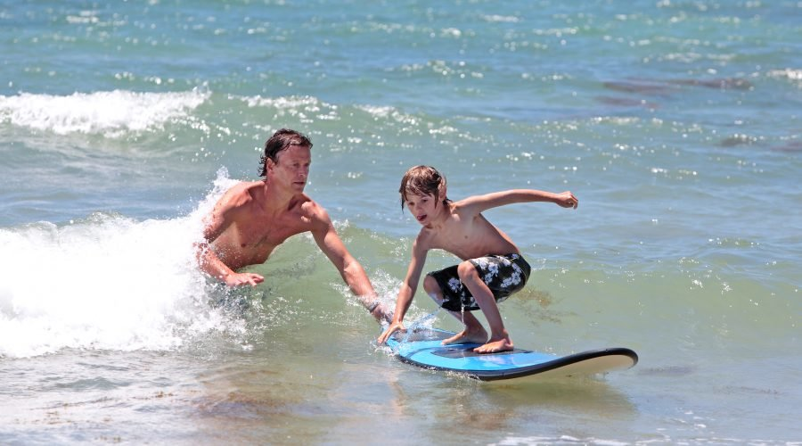father teaching son to surf