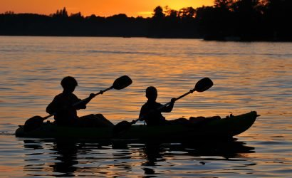 two people kayaking at sunset