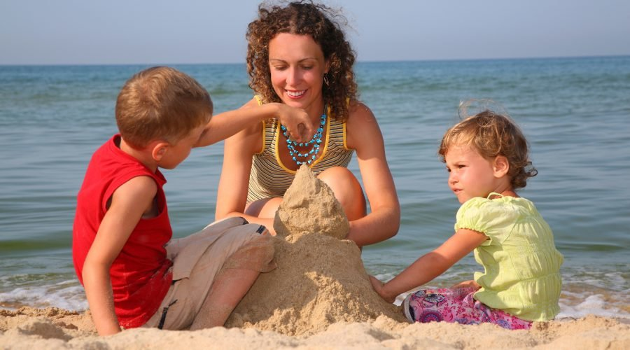 mom daughter son building sand castle on the beach