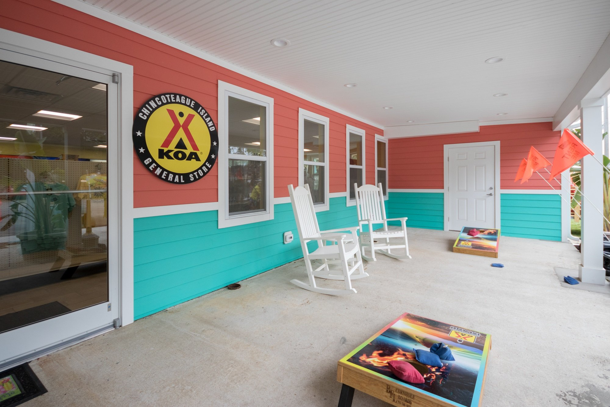 Chincoteague Island KOA General Store with bag toss game in front of bright coral and teal building
