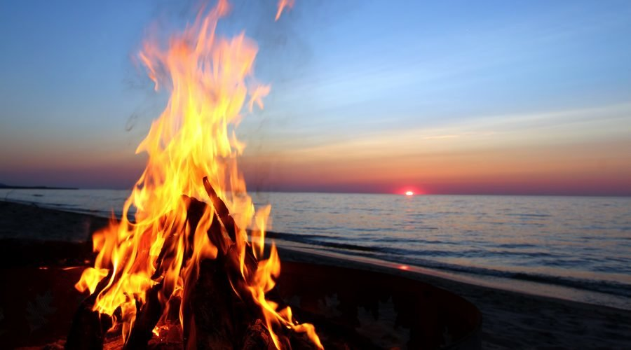 bonfire on the beach with the ocean and sunset in the background