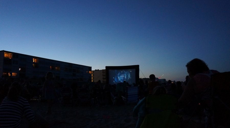 movie screen on the beach with people watching