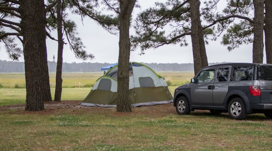 Chincoteague Island KOA campgrounds on delmarva car in front of tent camping with view of lighthouse between trees