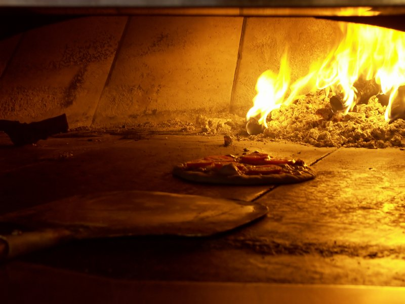 wood fired pizza in oven on International Beer and Pizza Day