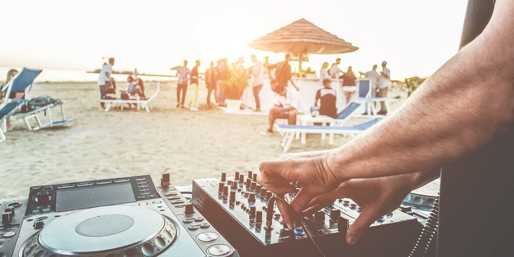 DJ playing on beach for crowd