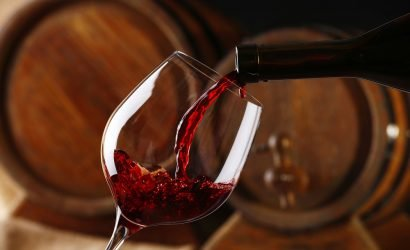 Red Wine Poured in front of Barrels