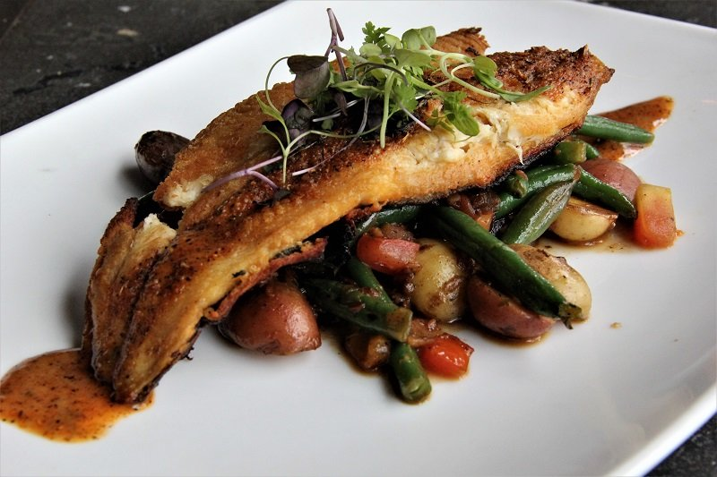 pan seared fish over vegetables