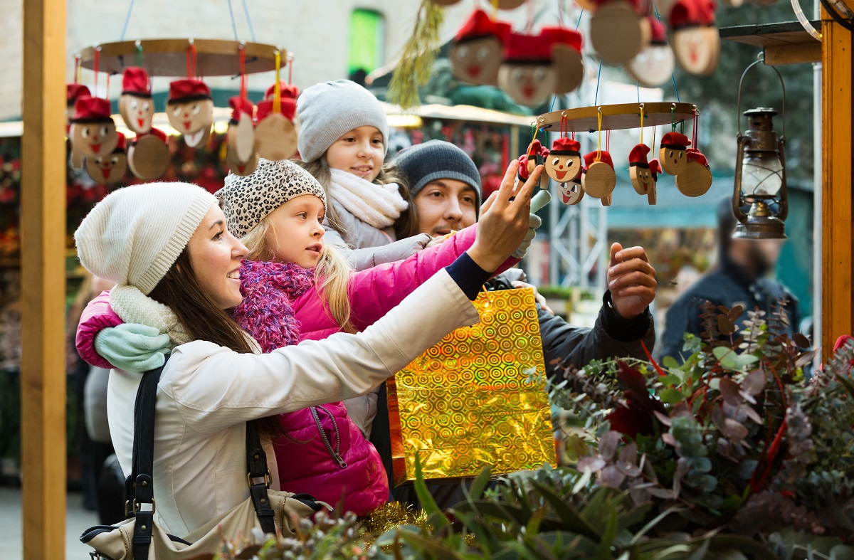 family of four admiring holiday ornaments at outside market