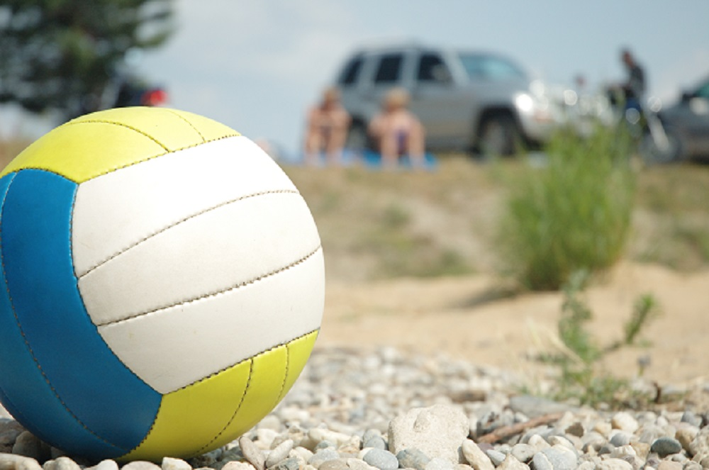red white blue volleyball outside on a bed of gravel