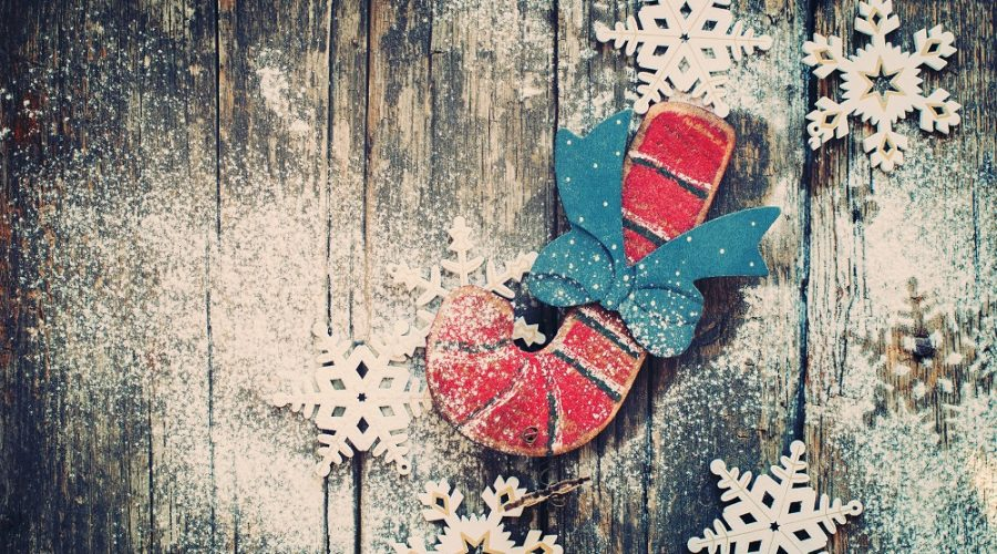 a handmade wooden candy cane and snowflakes on distressed wood background