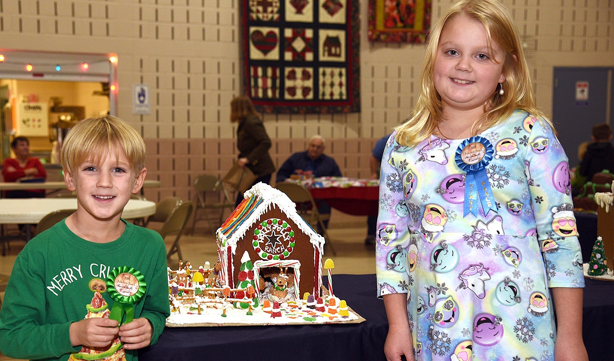 girl and boy standing next to the winning gingerbread house