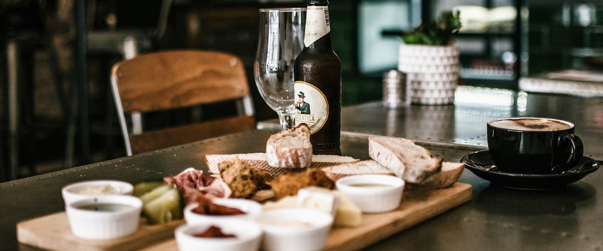 restaurant table set with cheese board and bottled beer