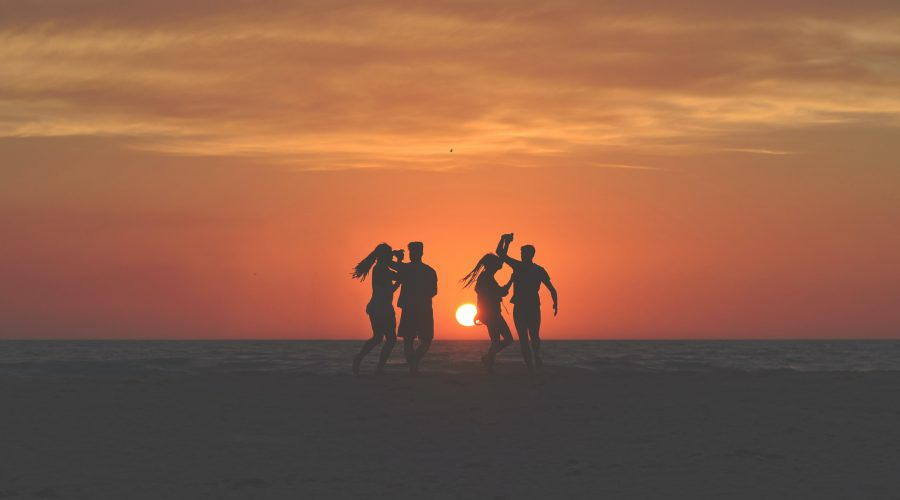 four people dancing on the beach